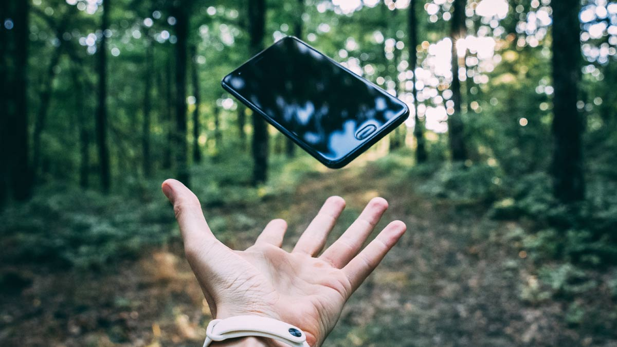 hand throwing mobile in the air against forest backdrop